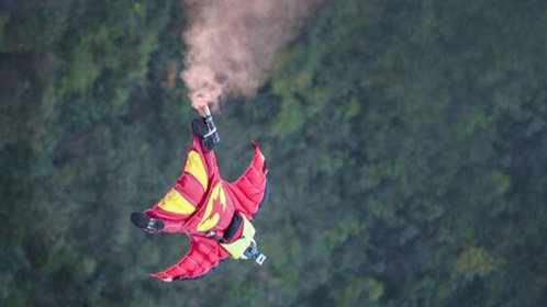 达人雪山跳下翼装飞行擦树梢而过